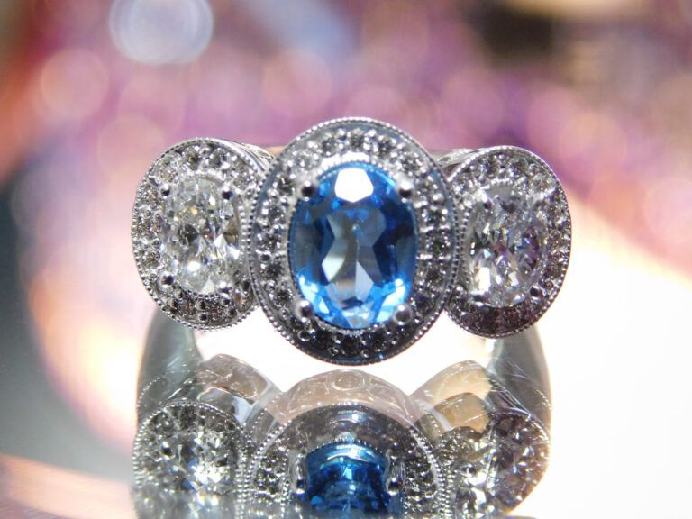 top view of white gold and tazinite and diamond ring with halo around all three stones