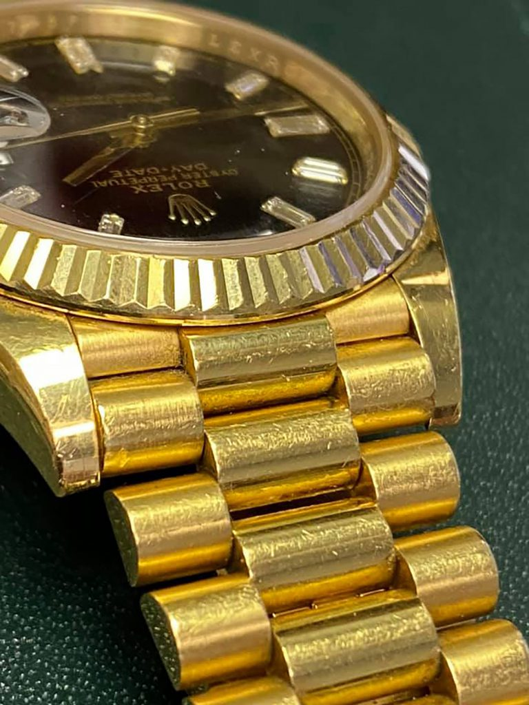 yellow gold Rolex watch covered in scratches and dings